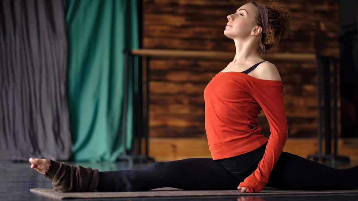 Woman doing yoga on biomat